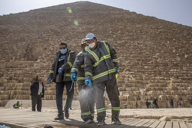 Municipal workers sanitize the Giza Pyramids as prevention measures due to the coronavirus outbreak, in Egypt, Wednesday, March 25, 2020.