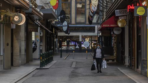 A lone shopper is seen carrying shopping bags as she walks down the usually busy Degraves Street laneway fame for its cafes and coffee as lockdown of Melbourne forces people to stay at home if not working due to the continuing spread of COVID-19. (Asanka Brendon Ratnayake)