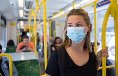 Woman wears face mask on public transport