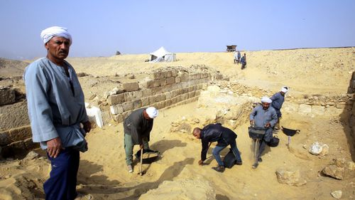 Egyptian excavation workers labor outside the tomb of an Old Kingdom priestess. (AAP)