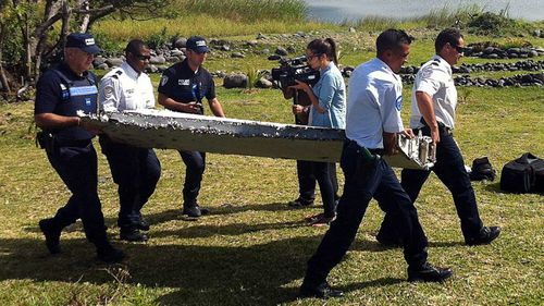 Officials carry away the debris after it was found on a beach on La Reunion.