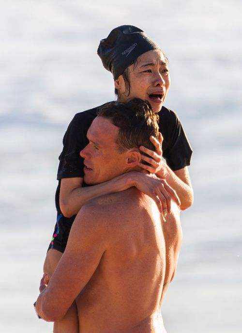 The terrified swimmer was carried from the beach in Andrew Reid's arms.