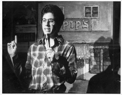 Jerry Seinfeld performing standup at a comedy club