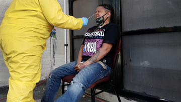 Naliber Tavares winces as she receives a COVID-19 test at the Whittier Street Health Center's mobile test site, Wednesday, July 15, 2020, in Boston's Dorchester section. The health center has administered free COVID-19 tests to over 5,000 people. The tests, administered since April 13, have been a popular service in Boston's low-income communities that have experienced high rates of infection. (AP Photo/Elise Amendola)