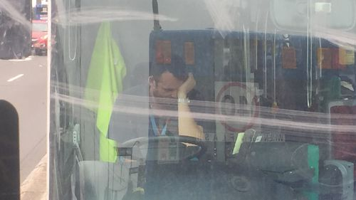 A bus driver sits at the wheel with his head in his hand after almost two hours in bumper-to-bumper traffic. (Supplied, Cherry Chen)