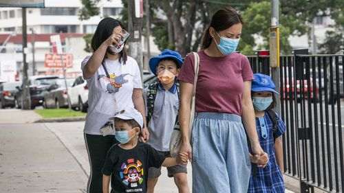 Students and parents wear face masks as they walk to school in Hurstville, in Sydney's south.