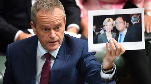 Leader of the Opposition Bill Shorten holds a photograph of Minister for Foreign Affairs Julie Bishop and chinese businessman Huang Xiangmo during Question Time in July. (AAP)