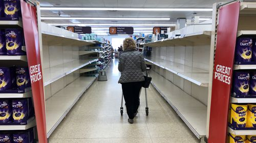 A shopper walks past empty shelves in a supermarket in the UK, where panic buying has also become a major issue.
