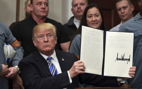 President Donald Trump holds up a proclamation on aluminum during an event. (AAP)