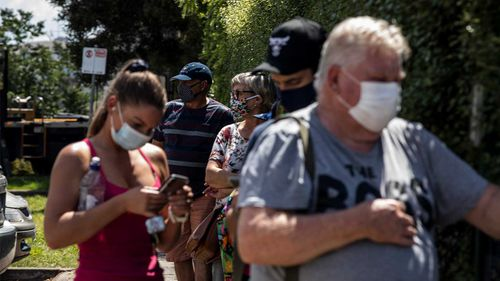 People wear face masks as they wait to receive a COVID-19 test outside the Sunbury Respiratory Clinic.