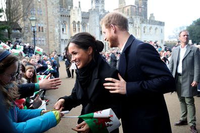 Prince Harry and Meghan Markle sign autographs and shake hands with children as they arrive to a walkabout at Cardiff Castle on January 18, 2018 in Cardiff, Wales.  (Photo by Chris Jackson/Chris Jackson/Getty Images)