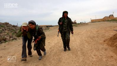 Tara Brown ducks for cover as she is guided along the front line by members of the YPJ.