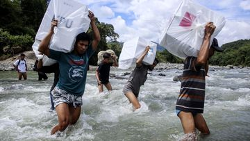 Indonesian election workers carry ballot boxes as they cross a river to deliver them to remote villages in Maros, South Sulawesi, Indonesia.