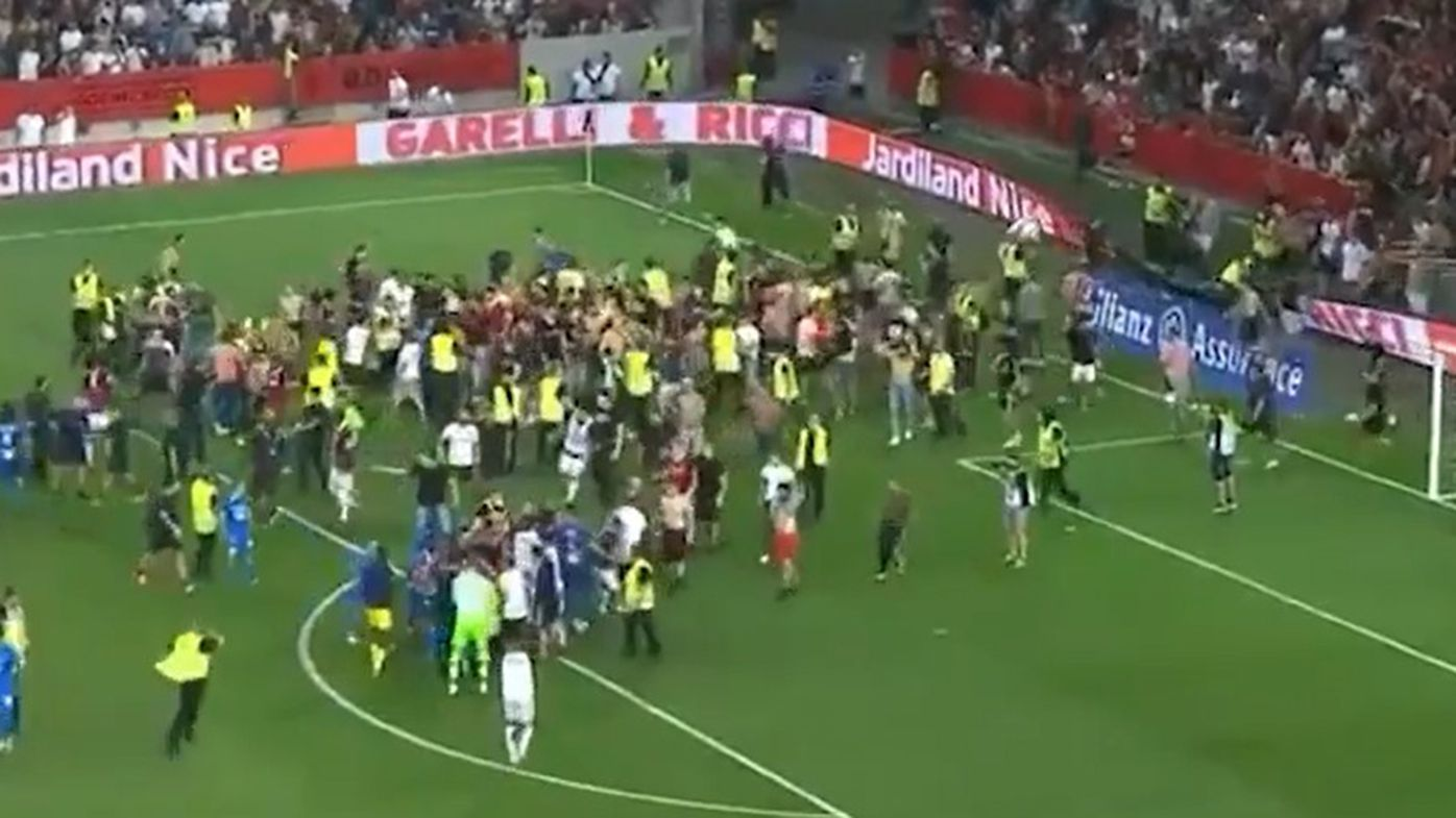 Fans invade the pitch as the match between Nice and Marseille is halted.