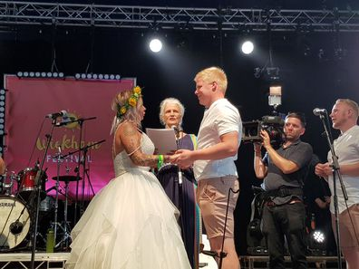 The couple saying their vows on the festival stage