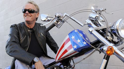 File photo from 2009, Peter Fonda, poses atop a Harley-Davidson motorcycle in Glendale, California.