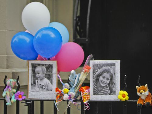 n this Oct. 27, 2012, file photo, photographs of 6-year-old Lucia Krim and her 2-year-old brother, Leo, are displayed alongside balloons and stuffed animals at a memorial outside the apartment building where they lived in New York. Opening arguments begin Thursday, March 1, 2018, for Yoselyn Ortega, the family's nanny charged with murder in the Oct. 25, 2012, deaths of the siblings. (AP Photo/Mary Altaffer, File)