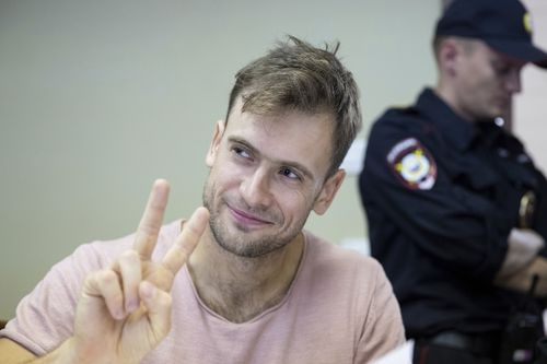 Pyotr Verzilov, a member of the feminist protest group Pussy Riot, gestures during hearings in a court in Moscow, Russia, Monday, July 23, 2018. Four members of the feminist protest group Pussy Riot, who had run onto the pitch dressed in police uniforms during the World Cup final, were sentenced in Moscow City Court on Monday. (AP Photo/Pavel Golovkin)