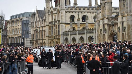 Crowds watch as the funeral cortege of Professor Stephen Hawking arrives. (EPA)