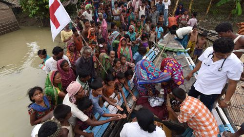 Officials distribute medicine to villagers in the flood affected Sagolikota area in India's north east. (AFP)