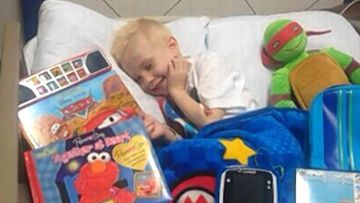 Jordan Bleimeyer surrounded by toys in hospital. (Facebook)