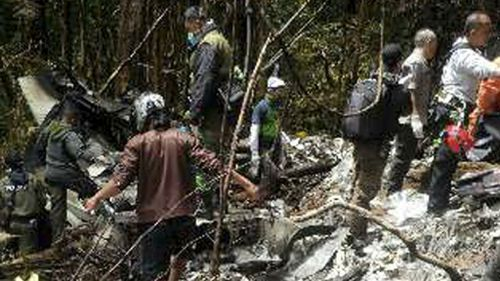 Officials and rescue workers gather by plane wreckage strewn across dense terrain. (AP)