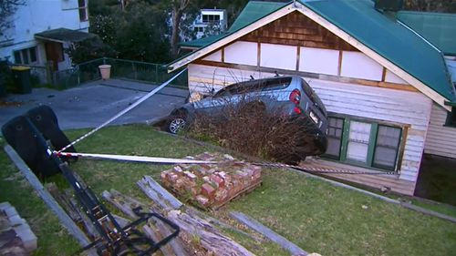 The driver was uninjured, however a crane will be required to remove the car. (9NEWS)