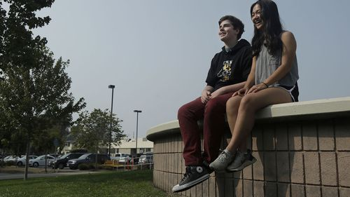 Alameda High School students Henry Mills, left, and Kristen Wong pose for photos on the school's campus in Alameda