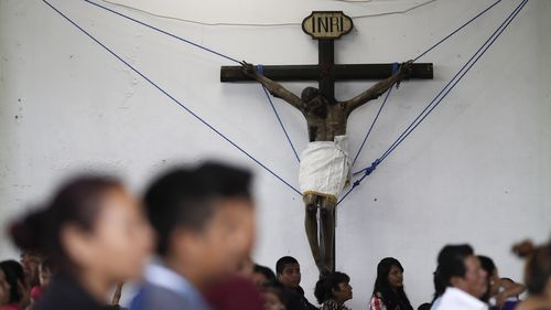 A crucifix, recovered from a collapsed church, is held up by ropes inside an auditorium during a Mass, in Tepeojuma. (AAP)