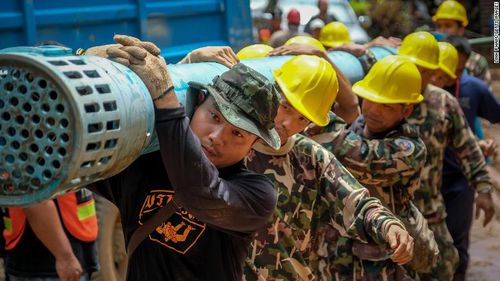 Rescue workers carry water pumping equipments into Tham Luang Nang Non cave on Sunday. Picture: Getty