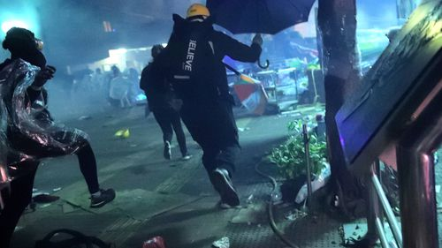 Protesters run outside of Hong Kong Polytechnic University as police storm the campus in Hong Kong
