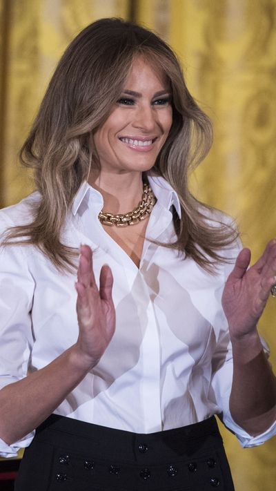 Melania Trump in a white shirt and black Ralph Lauren collection skirt.