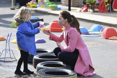 Kate Middleton, Duchess of Cambridge talks with a child in the water area of the playground during a visit with Prince William to School21, a school in east London, Thursday March 11, 2021