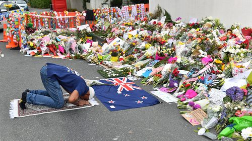A muslim worshipper prays at a makeshift memorial near the Al Noor Mosque on Deans Rd in Christchurch.