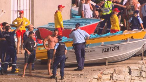 Police and life savers gather on the beach after the Russian DJ drowned.