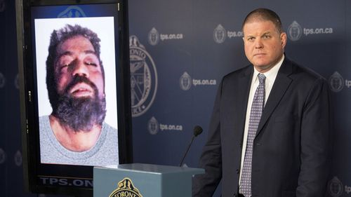Det. Hank Idsinga, lead investigator in the case against Bruce McArthur, stands with a photo of an unidentified man. (AP)