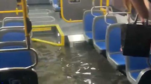 Water fills a New York bus as it drives through floodwaters.