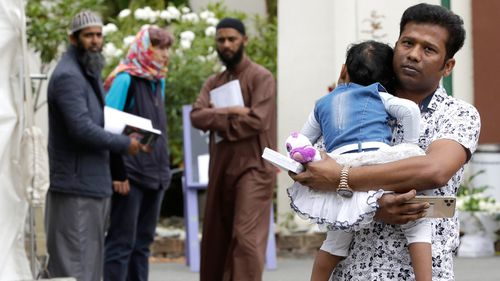 A father carries his daughter as he leaves the the Al Noor mosque in Christchurch, New Zealand.  A national memorial in New Zealand to commemorate the 51 people who were killed when a gunman attacked two mosques one year ago has been cancelled due to fears over the new coronavirus.