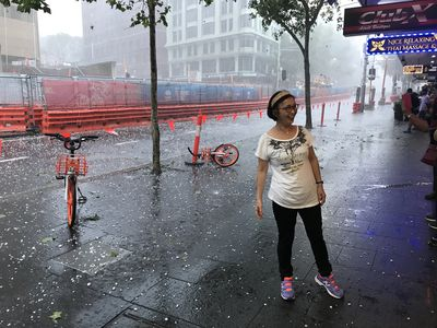 A woman surveys the hail on George Street in Sydney's CBD.