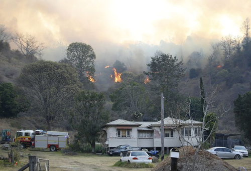 Fire and Emergency crew battle bushfire near a house in the rural town of Canungra in the Scenic Rim region of South East Queensland, Friday, September 6, 2019. (AAP Image/Regi Varghese)