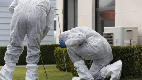 Police forensics officers scouring a lawn near a Queen St house in which three children were found dead.
