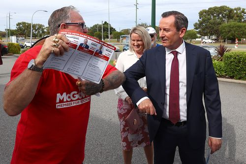 West Australian Premier Mark McGowan and his wife Sarah McGowan bump elbows with a campaigning volunteer.