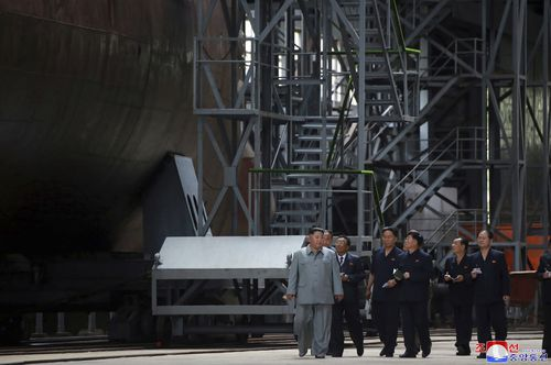 North Korean leader Kim Jong Un, left, inspects a newly built submarine to be deployed soon, at an unknown location in North Korea.
