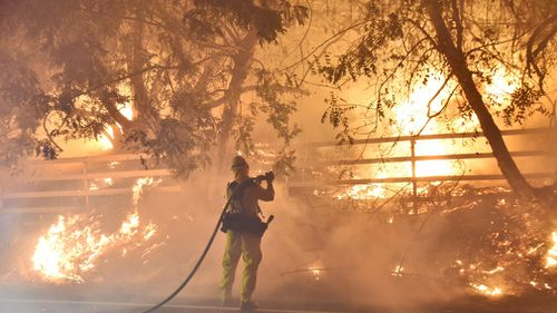 A firefighter works to put out a blaze early in Santa Paula, California. (AAP)