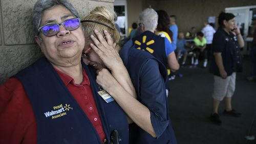 Walmart employees comfort each other after the shooting.