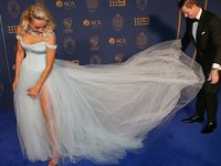 Steve Smith helps his partnerDanielle Willis with her dress.