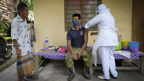 A nurse administers a Pfizer COVID-19 vaccine to a farmer outside his home in rural Sabab Bernam, central Selangor state, Malaysia.
