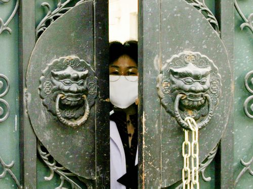 In this 2004 photo, a quarantined medical worker, wearing a face mask to protect against the Severe Acute Respiratory Syndrome (SARS) virus, peeks out of the entrance gate of the national institute of virology to pick up clothes and lunch boxes in Beijing, China.