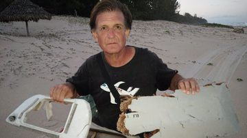 Blaine Gibson holding new pieces of debris possibly belonging to the missing Malaysian Airlines plane MH370, found on Nosy Boraha Island, Madagascar. (AAP)