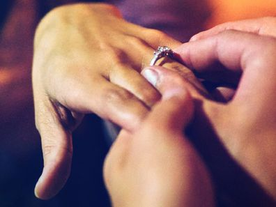 Man placing ring on woman's finger following proposal